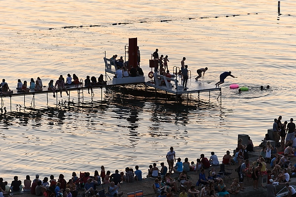 The Memorial Union Terrace and its swimming pier — one of the campus's most popular spots — attract a crowd as daylight wanes and people await the annual Rhythm and Booms fireworks show held each summer across the lake at Warner Park.