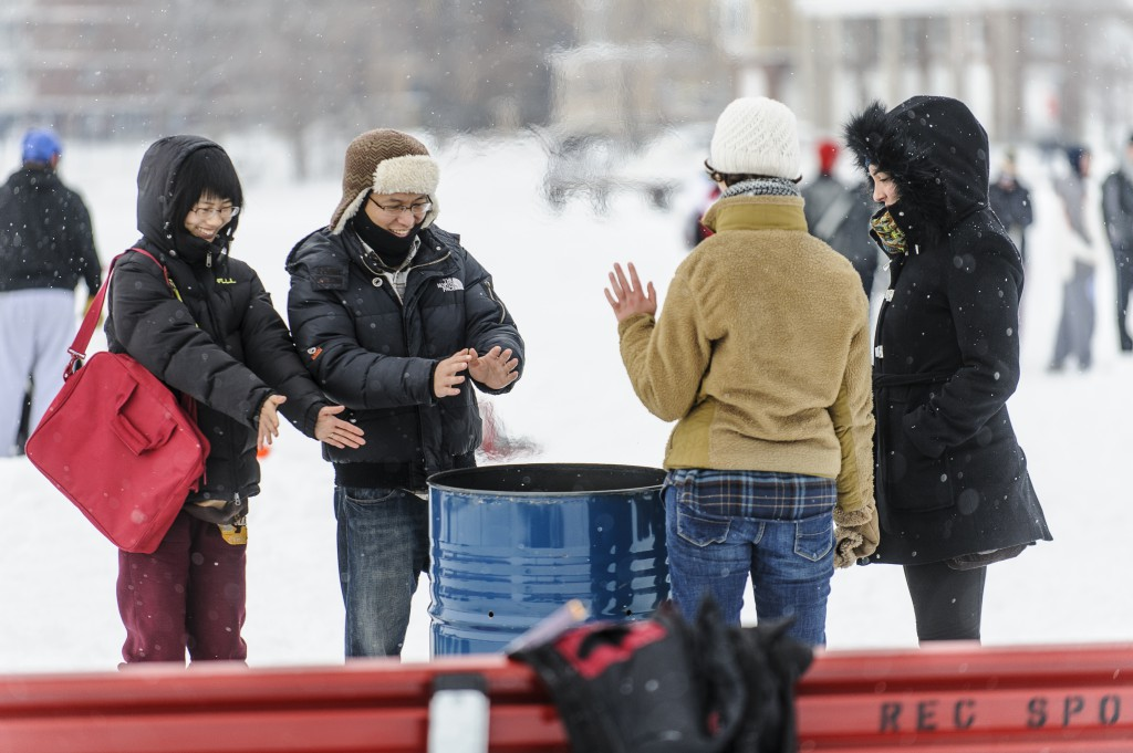 Spectators take a break to warm their hands at a fire as the snow comes down.
