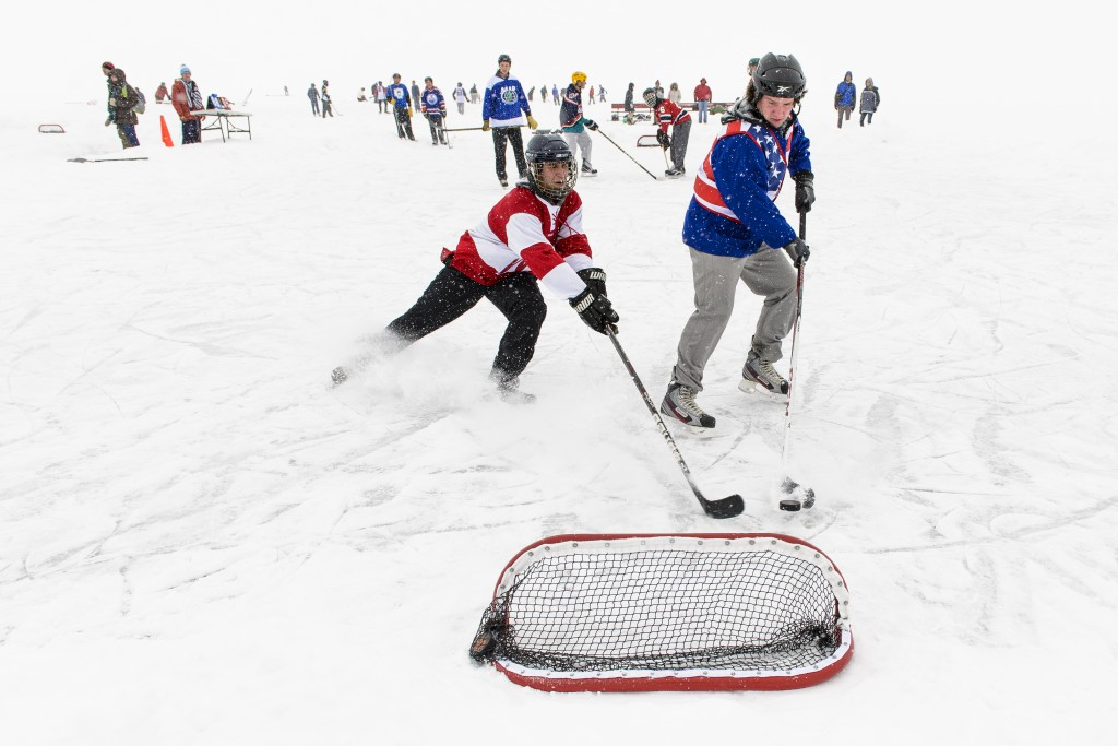 Teams of UW students stay warm and get into the Olympic spirit by playing hockey during the carnival's tournament on Lake Mendota.