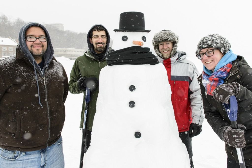 Bundled against the cold, a group of UW-Madison students are pictured with a carrot-nosed snowman they built on the lake.