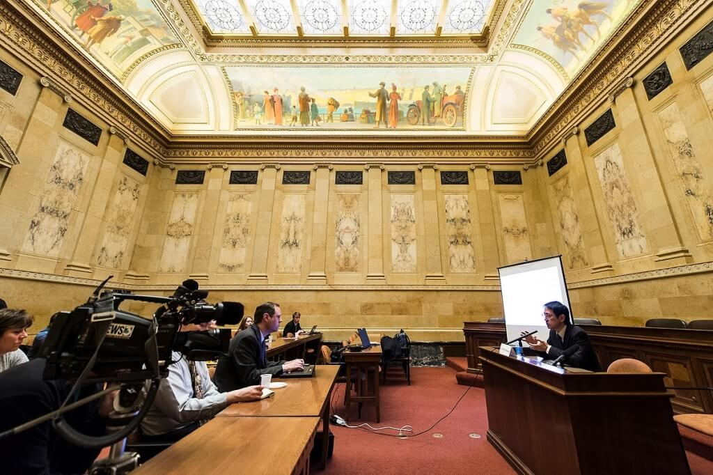 Legislators and staff gathered in an ornate hearing room at the state Capitol listen as UW virologist Yoshihiro Kawaoka explains his work to deter serious diseases such as Ebola.