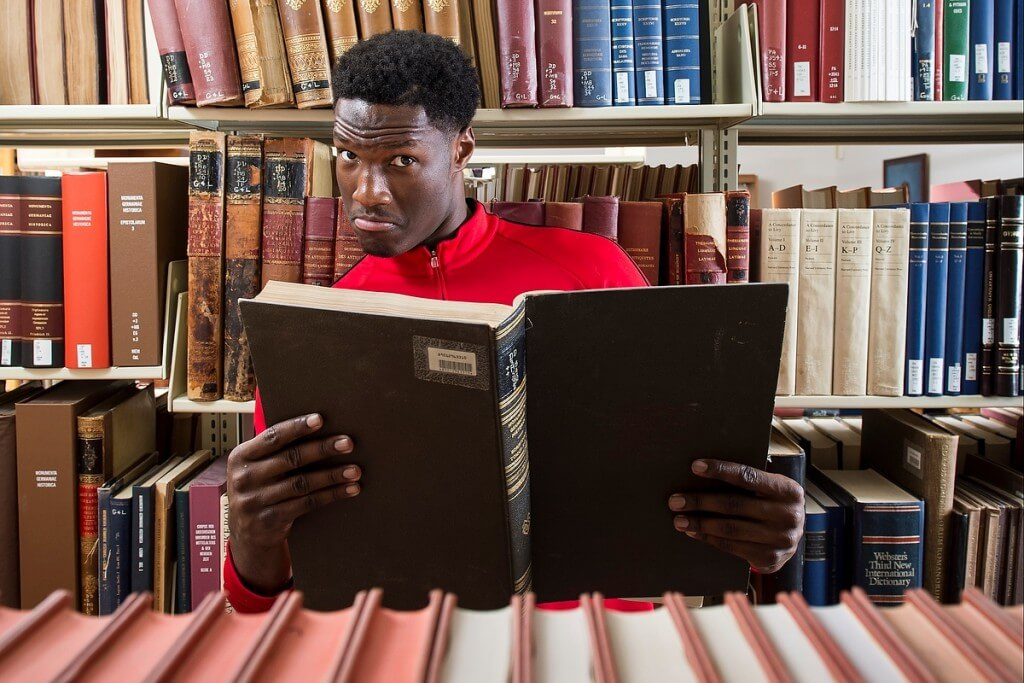 No doubt adding to his already impressive vocabulary, Badger basketball player Nigel Hayes browses books during a photo shoot for a UW-Madison Libraries READ poster.