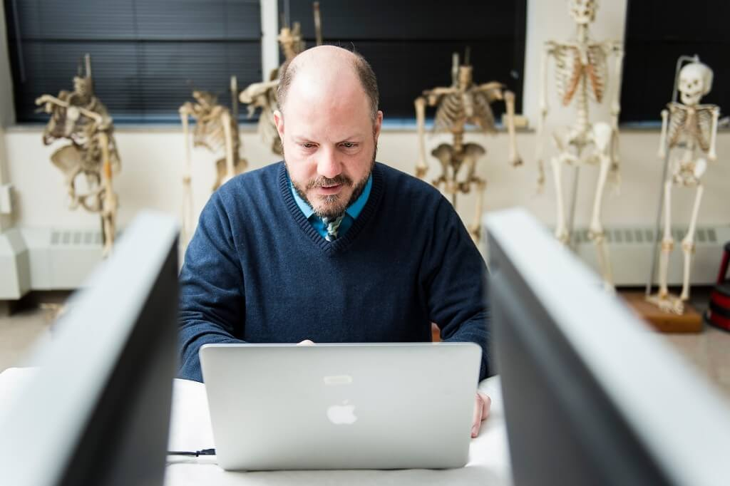 As skeletons hang out close by, UW paleoanthropologist John Hawks types on a laptop in the Biological Anthropology Lab in the Sewell Social Sciences building.