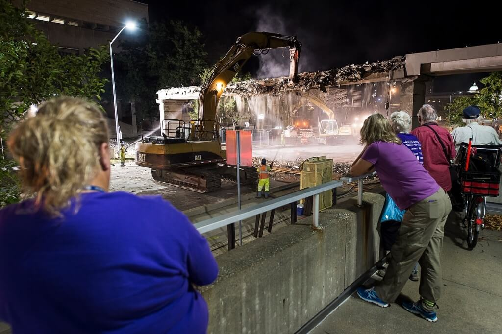 A 1970s-era bridge comes tumbling down in August as spectators watch construction workers demolish the deteriorating structure between the Mosse Humanities Building, left, and Vilas Hall, foreground.