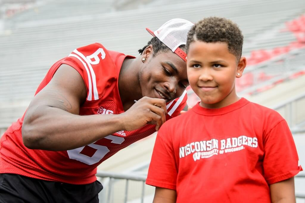 It's the thrill of this young fan's life as Badgers running back Corey Clement signs his T-shirt during Family Fun Day at Camp Randall Stadium.