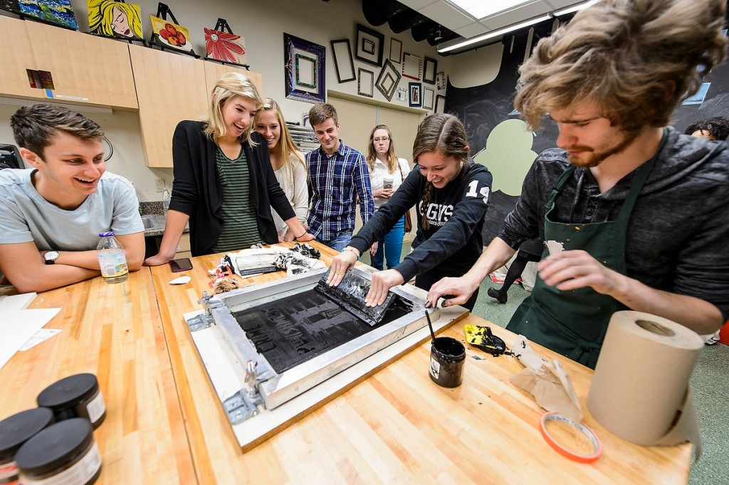 """Tangible results are revealed as students in a business school class use silk-screening techniques at Wheelhouse Studios to create posters related to """"Just Mercy,"""" this year's selection for Go Big Read."""