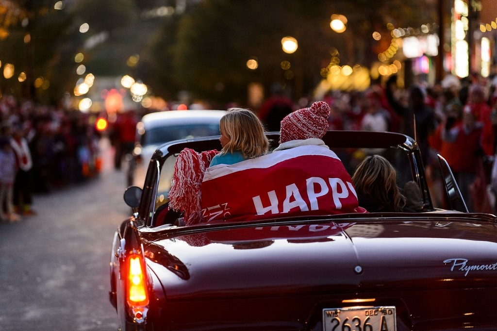 Huddling under a banner (full disclosure: Happy Homecoming), children ride in the back of a vintage car and wave to thousands of spectators lining State Street during the annual Homecoming Parade.