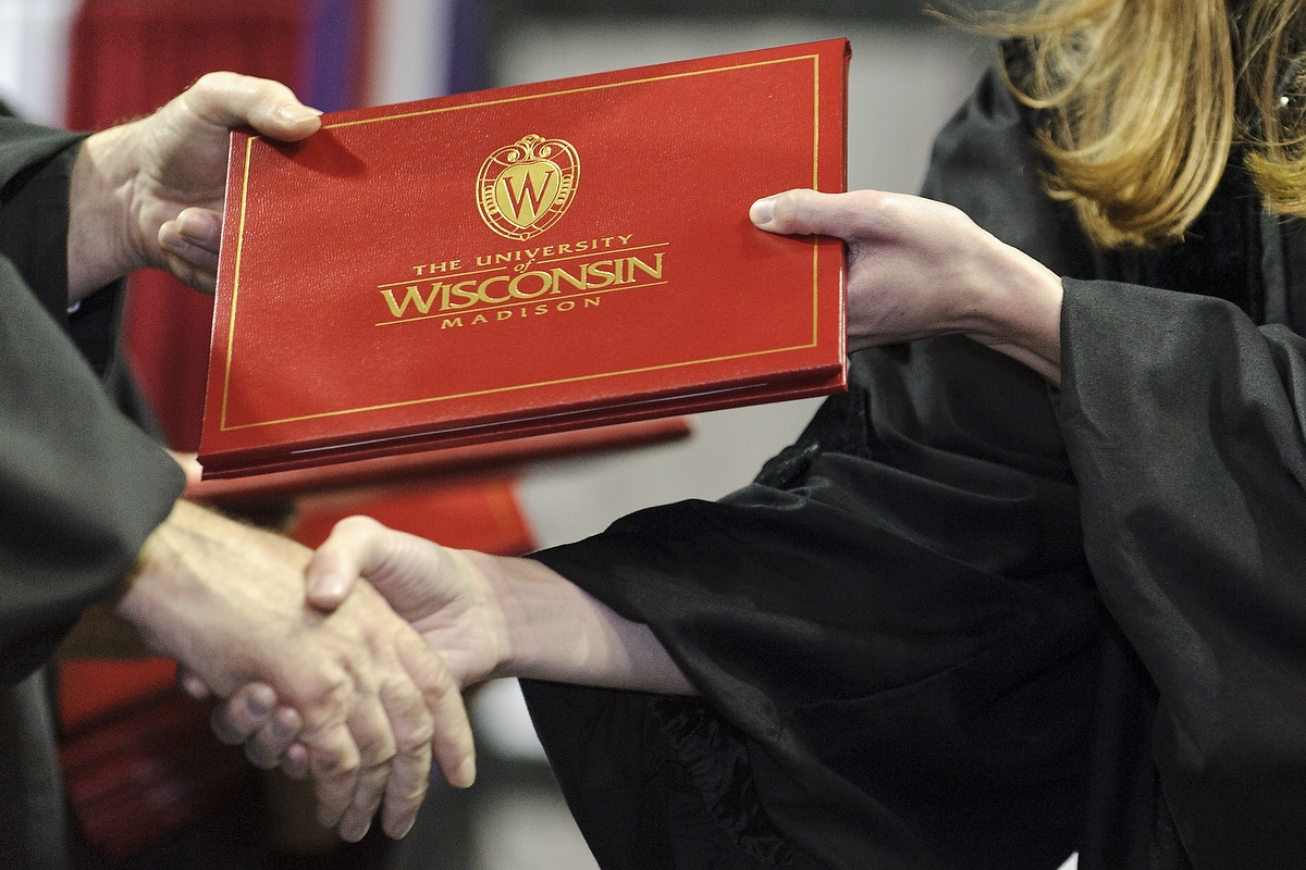 A graduate student receives a doctoral degree during UW–Madison Commencement at the Kohl Center in 2013.