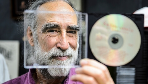 Soon-to-retire faculty member Jim Leary, professor of folklore and Scandinavian studies, peers through the liner-note section of a CD case in his office at Sterling Hall. Leary was recently nominated for a Grammy Award in the category of