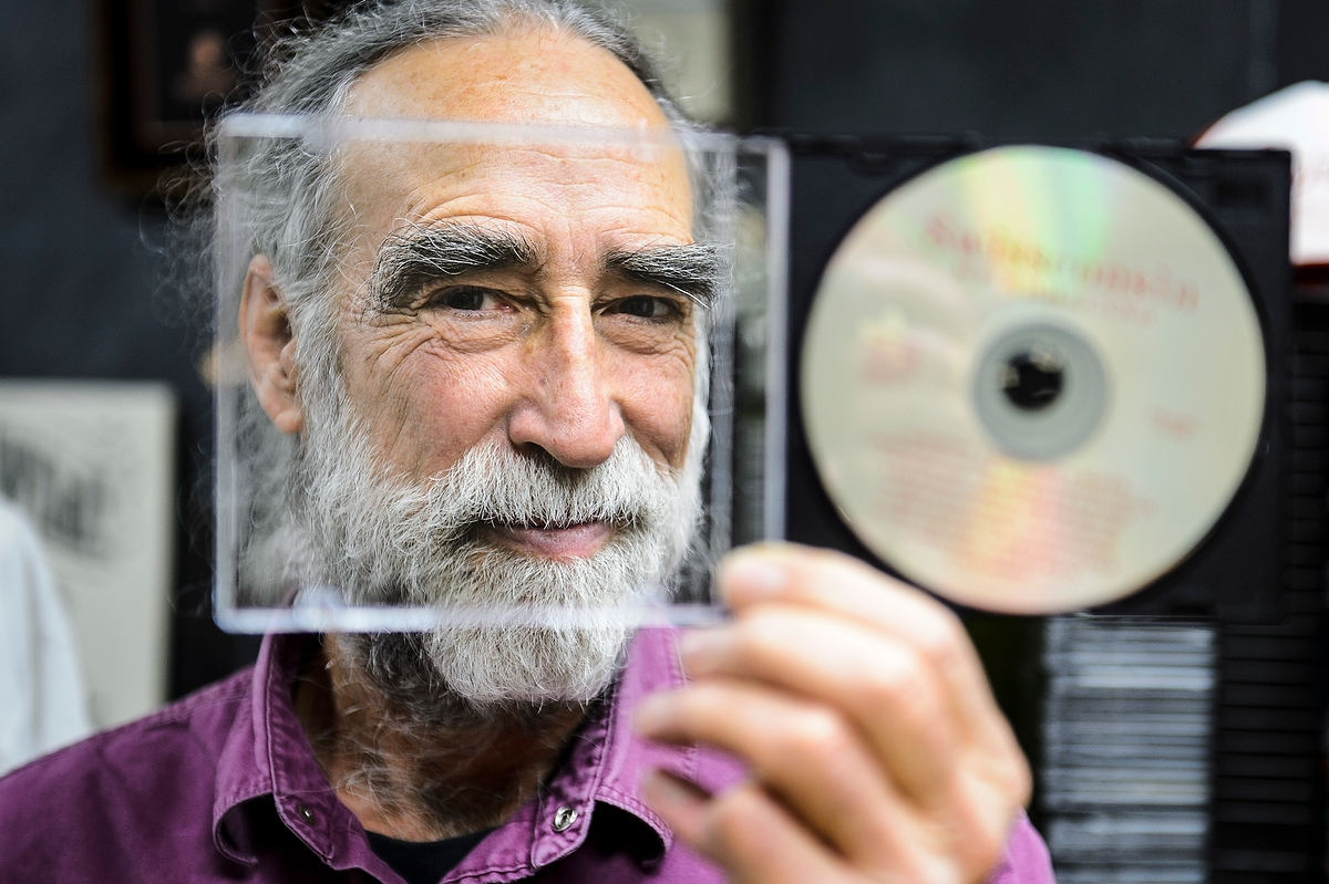 """Soon-to-retire faculty member Jim Leary, professor of folklore and Scandinavian studies, peers through the liner-note section of a CD case in his office at Sterling Hall. Leary was recently nominated for a Grammy Award in the category of """"Best Album Notes"""" for his work on the book and five CD/one DVD project """"Folksongs of Another America: Field Recordings from the Upper Midwest, 1937-1946."""""""