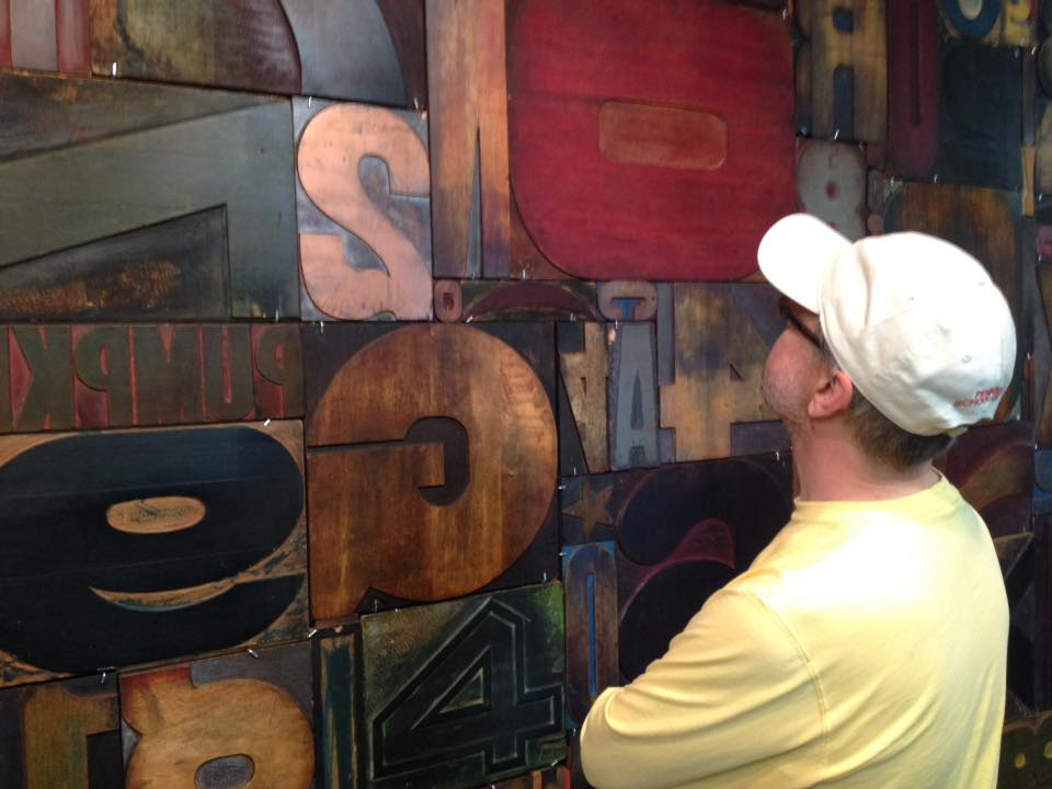 A visitor observes a display of wood type samples at the Hamilton Wood Type & Printing Museum.