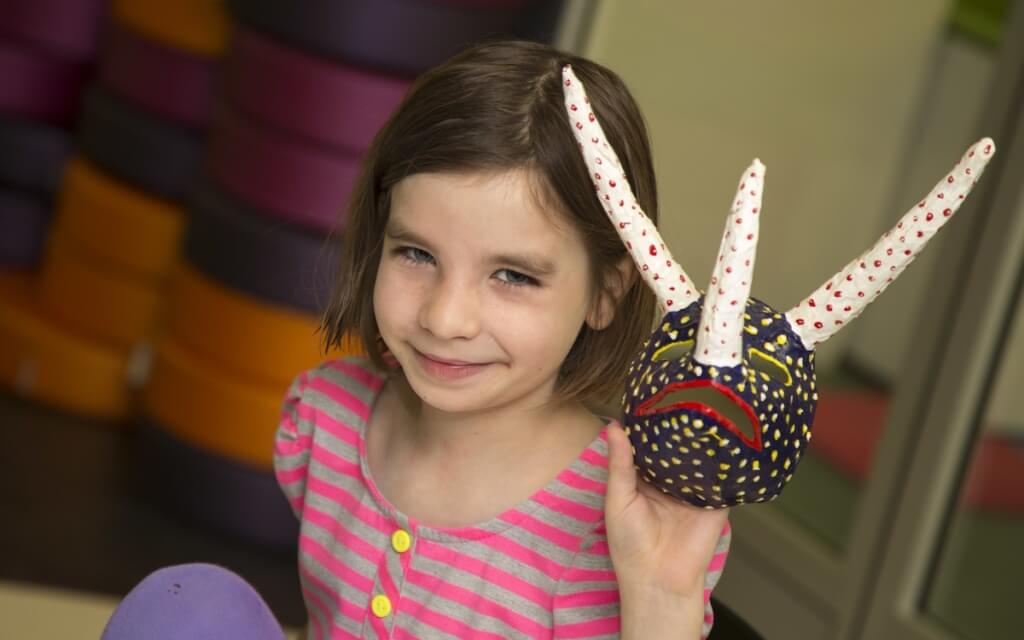 Nine-year-old Grace Halverson, daughter of UW–Madison education researchers Erica and Rich Halverson, shares a handmade mask created at The Bubbler.