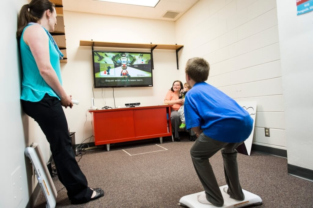 Xavier Hansen stands on a Wii Connect balance board and practices a Wii ski jump pose while mirroring his body position to match that of a video-game shape displayed on a computer monitor.