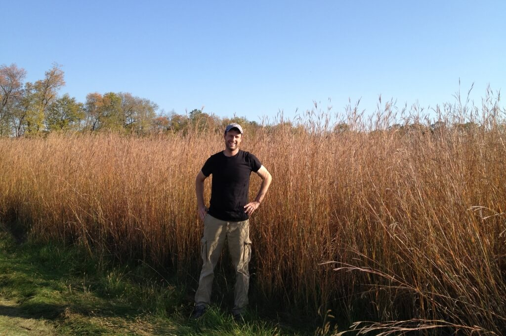 Peter Blank standing in front of a monoculture of Big Bluestem.