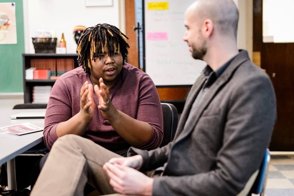 Manuel Herrero-Puertas, right, program coordinator for UW–Madison's Great World Texts in Wisconsin, talks with student Richard Lafford at New Horizons for Learning, a charter school based at Shorewood High School near Milwaukee.