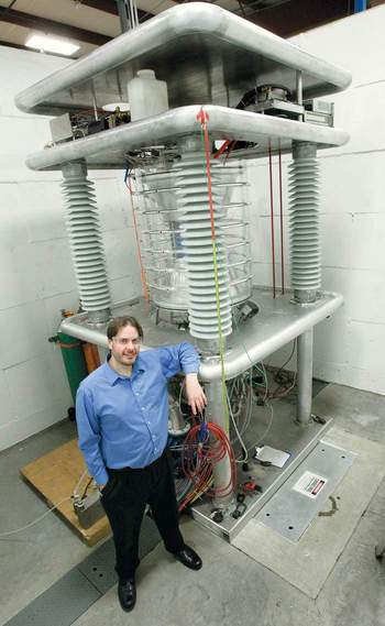 SHINE CEO Greg Piefer with a working prototype of the neutron generator he invented, which will be used to make moly-99 at the planned Janesville plant.