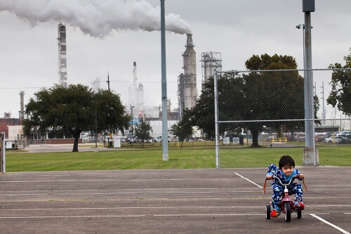 Chrisangel Nieto, age 3, rode his tricycle in front of the Valero refinery in Houston. This refinery processes almost 7 million tons of carbon per year, most of which will end up in the atmosphere as carbon dioxide.
