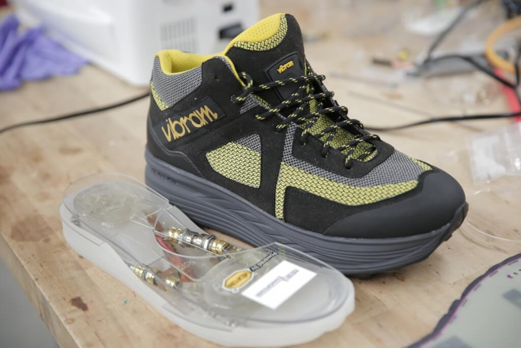 A shoe sole with an embedded energy harvester sits next to a first practical footwear energy harvester developed by the UW–Madison researchers' startup company, InStep NanoPower, and Vibram.