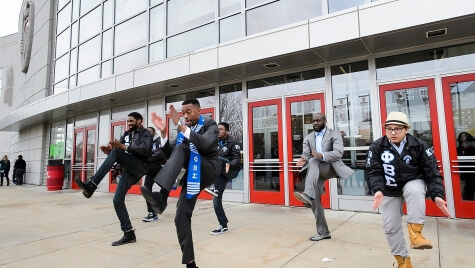 A graduate performs a step routine with his Phi Beta Sigma fraternity brothers following UW-Madison's 2015 winter commencement ceremony.
