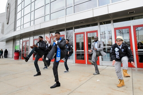A graduate performs a step routine with his Phi Beta Sigma fraternity brothers following UW–Madison's 2015 winter commencement ceremony.