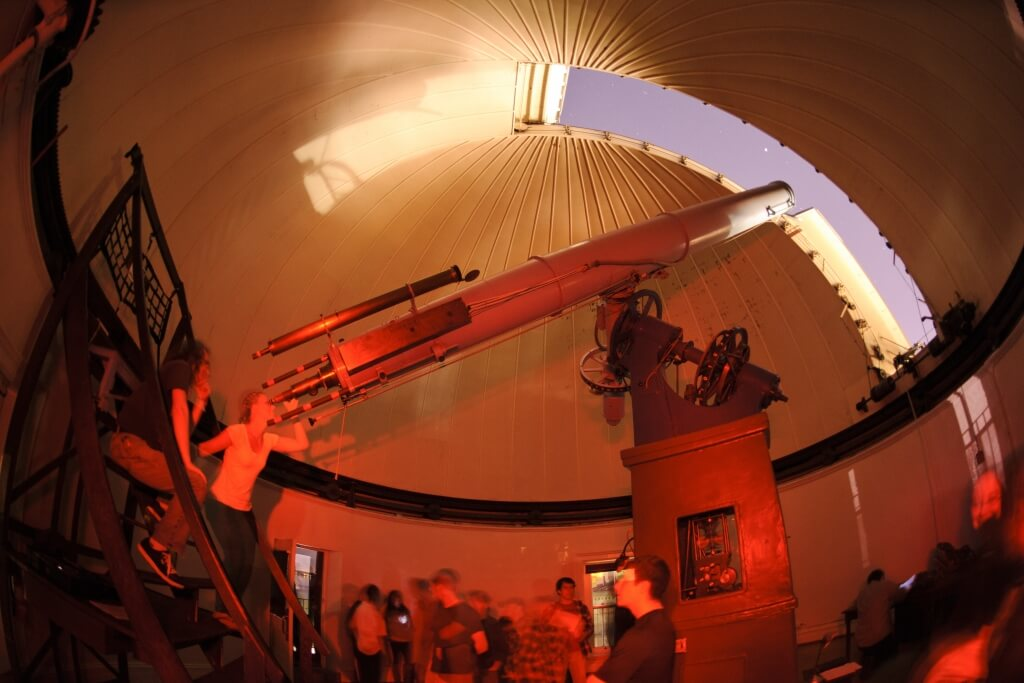 With moonlight shining in an open slit of the Washburn Observatory dome, the general public takes advantage of a once-monthly opportunity for nighttime public viewing of the stars using the observatory's vintage telescope in 2012.