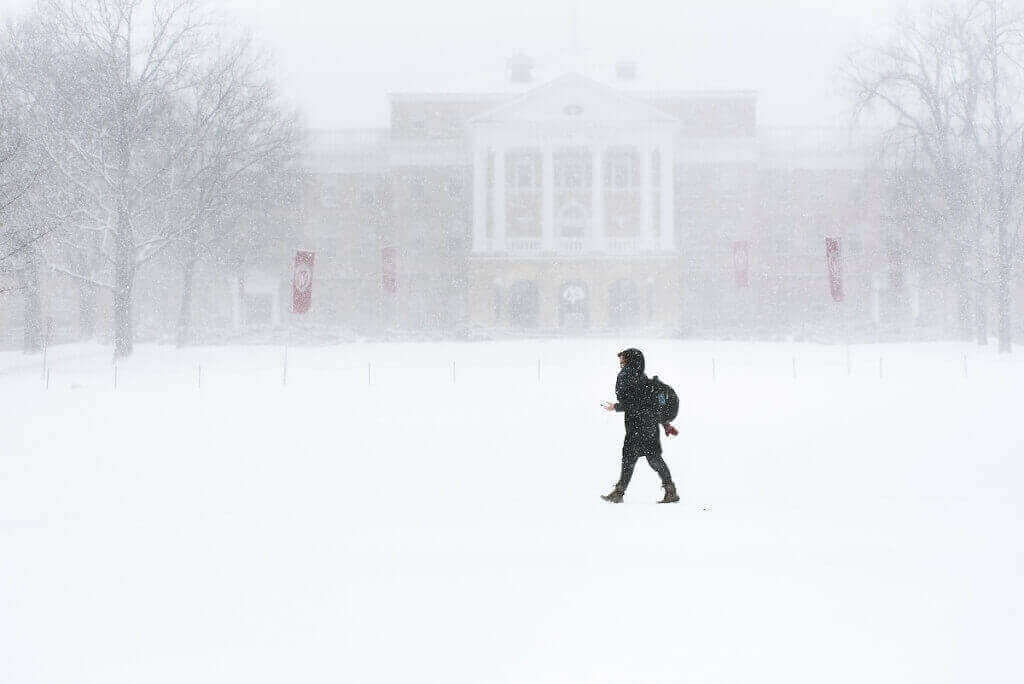 A pedestrian walks across Bascom Hill during a winter snowstorm with whiteout conditions on March 1. In the background is Bascom Hall and several W crest banners.