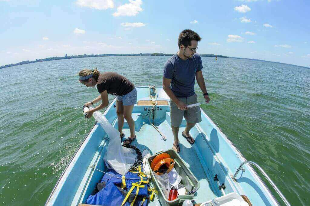 Center for Limnology grad student Jake Walsh and UW–Madison undergrad Carly Broshat use plankton nets to take samples of Daphnia pulicaria and spiny water flea in Lake Mendota.