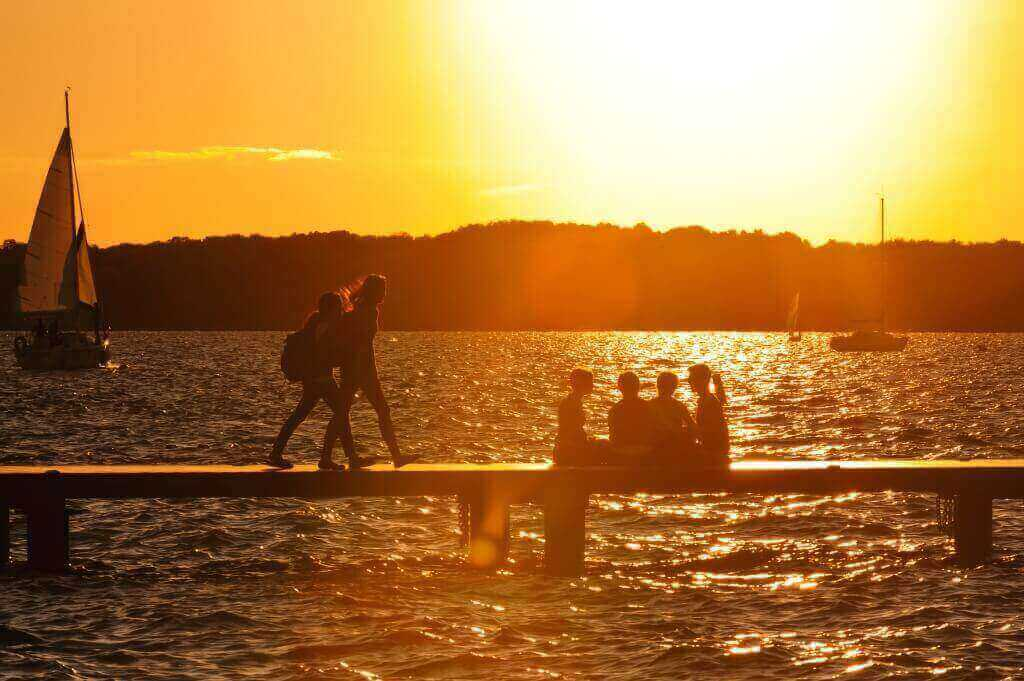 As the sun sets, UW–Madison students and visitors enjoy a cool summer evening on a Lake Mendota pier in July 2013.