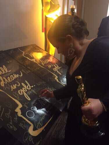 "UW-Madison alumna Nicole Rocklin, seen signing a poster backstage, was one of the producers of the movie ""Spotlight,"" which won Best Picture at the 88th Academy Awards on Feb. 28."