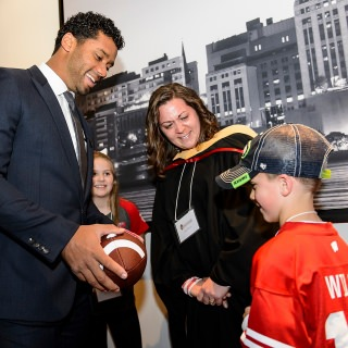 Commencement speaker Russell Wilson, Super Bowl winning quarterback for the Seattle Seahawks and former Badger football star, talks with Leah Olson, graduating with a master's in social work, and  her son, Dylan.