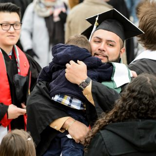 Graduate Salvador Zuniga gives a hug to his nephew before taking his seat on the field.