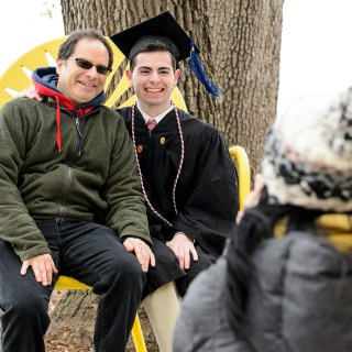 Graduate Zack Rosen is pictured with his father in a jumbo chair on the Memorial Union Terrace after commencement.