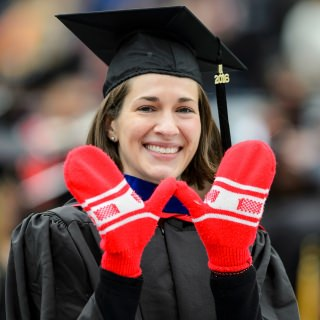 Graduating with an executive MBA in the School of Business, Amy Lee displays a mitten-handed W sign.