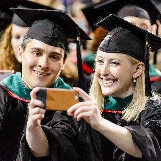 Graduates celebrate with a photo.