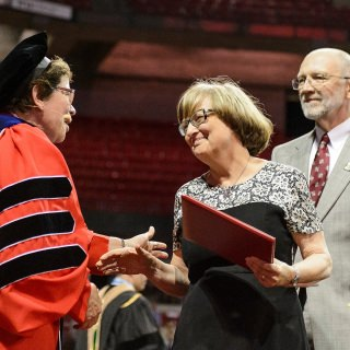 Chancellor Rebecca Blank greets the parents of graduate student Craig Schuff as they received his posthumous degree during Friday's commencement exercises at the Kohl Center. Schuff died in October, months away from completing his Ph.D. in nuclear engineering.