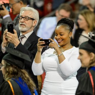 Proud family members capture the moment during commencement exercises for graduate and professional students Friday at the Kohl Center.