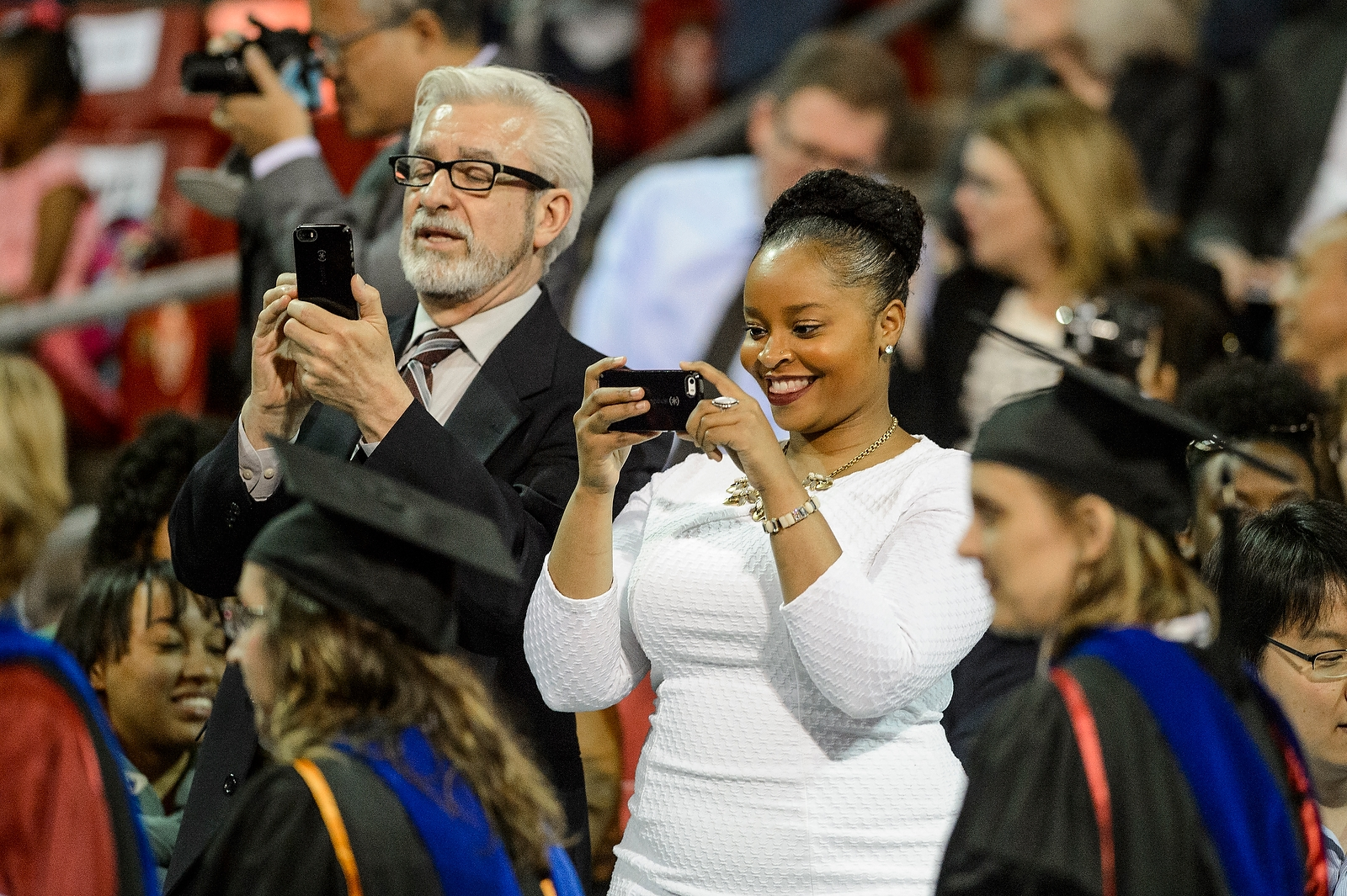 Proud family members capture the moment during commencement exercises for graduate and professional students Friday, May 13, at the Kohl Center.
