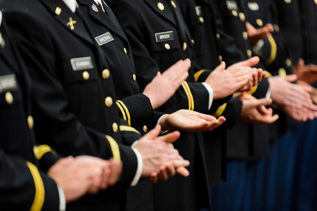 Photo: Closeup of uniformed people clapping