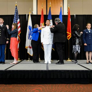 Family members help with a pinning ceremony as graduates from UW-Madison's Army, Navy and Air Force ROTC units participate in an officer commissioning ceremony at Gordon Dining and Event Center. Pictured from left to right are Army Second Lieutenant Josh J. Blusko of Mosinee, Wisconsin; Navy Ensign Benjamin N. Fritz of Lakeville, Minnesota; and Air Force Second Lieutenant Brienna N. Herdrich of West Bend, Wisconsin. The event followed UW-Madison's spring commencement ceremony and formally recognized 37 graduating members as officers in the military.