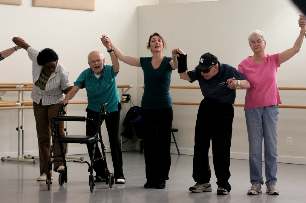 Photo: Group of people with Parkinson's lifting arms