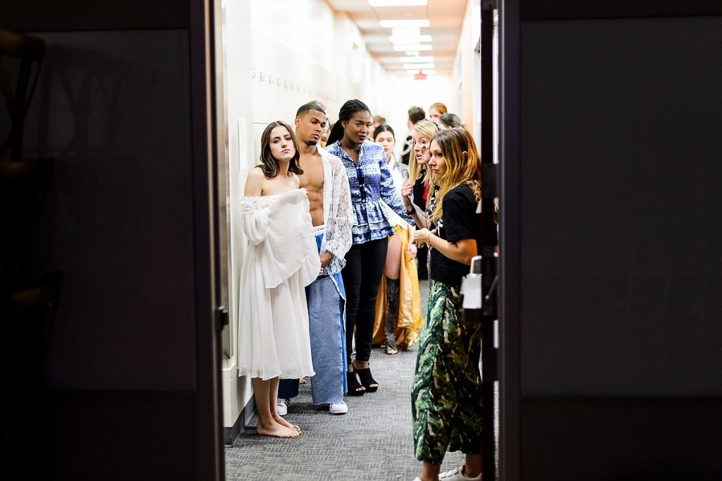 "Wearing student-designed clothing, models wait backstage before the start of ""Threads: IMPACT."""