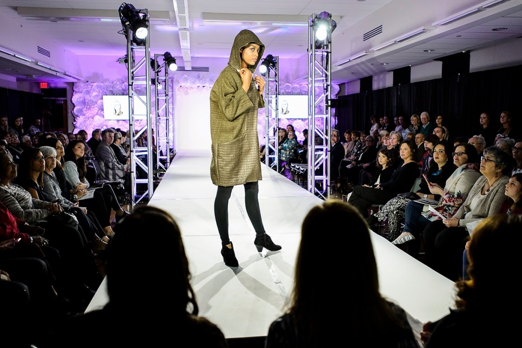 Model Zashary Torres walks the runway showcasing a cozy coat.