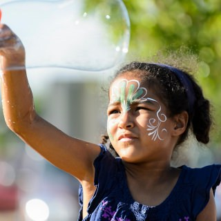 At a table sponsored by the group Adult Role Models in Science, Hallie Justice, 6, waves a large soap bubble wand.