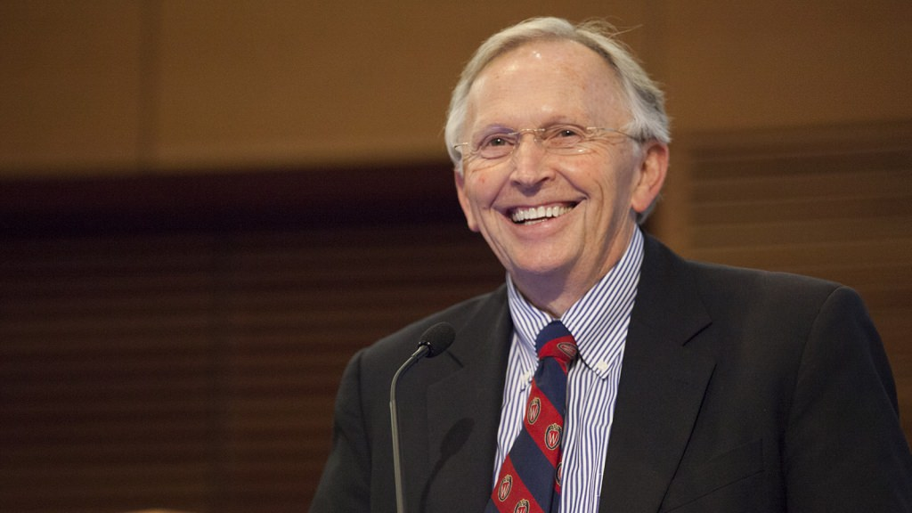 Grey-haired man in glasses, suit and red and blue tie, from behind podium, smiles towards his audience