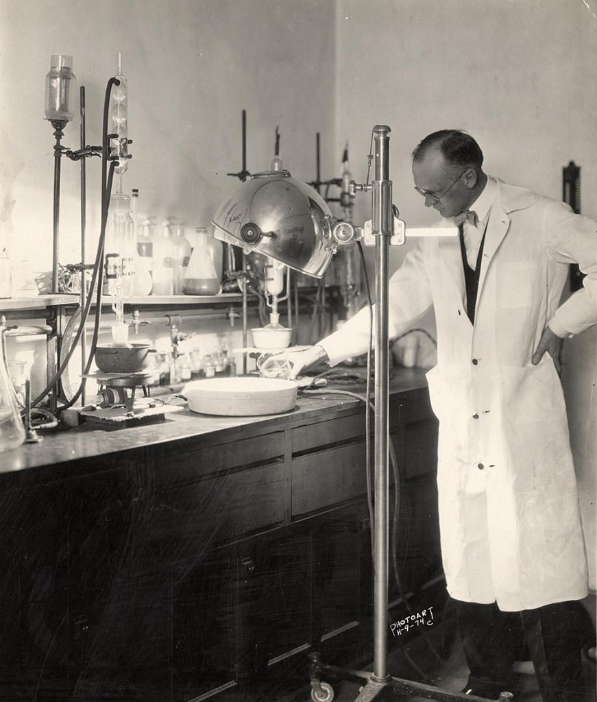 black and white photo of man in white lab coat, glasses, bow tie, pouring liquid into shallow container. Surrounding are various tools and containers, and a big floor lamp on wheels, consistant with old-fashioned lab