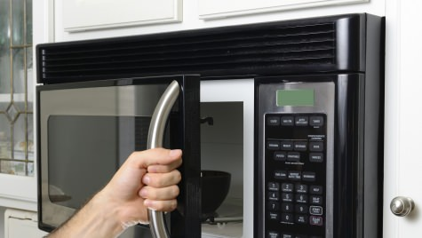 Photo: Hand opening microwave oven
