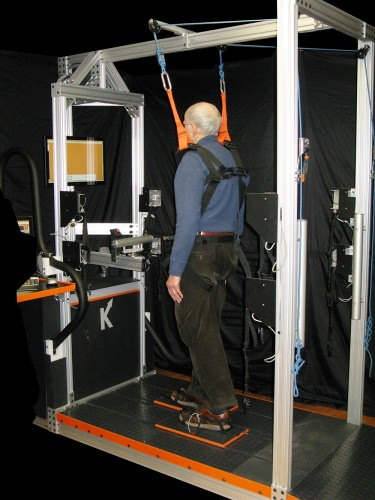 man being held up with straps from above, treadmill underfoot