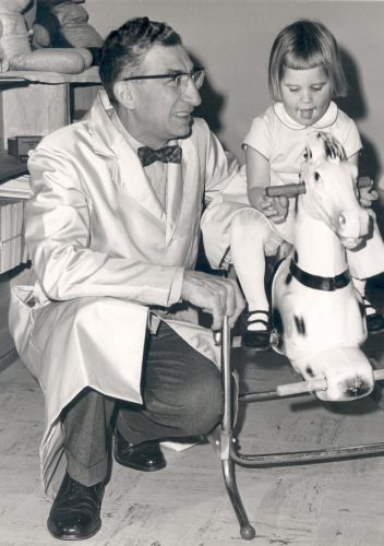 Photo: Harry Waisman with girl on rocking horse