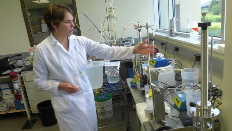 Photo: Melissa Suzuki at Aldevron explains a membrane-based flow filtration system that quickly reduces the volume of a solution using low-pressure osmosis.
