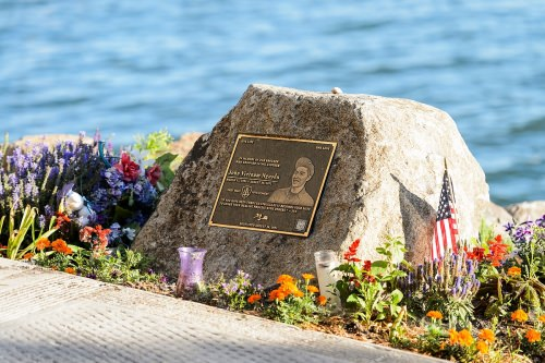 """A memorial to former UW–Madison student John """"Vietnam"""" Nguyen is pictured as the morning sun shines on Lake Mendota near the University of Wisconsin–Madison shoreline during summer on July 14, 2016. Nguyen, a member of the fifth cohort of the First Wave Spoken Word and Hip-Hop Arts Learning Community, lost his life while saving a friend from drowning on Aug. 30, 2012. (Photo by Jeff Miller/UW-Madison)"""